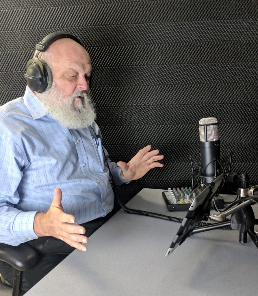 Old man with white beard recording voiceover